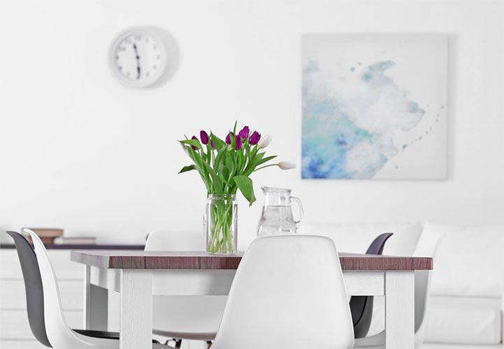 A dining room with a pale blue canvas print on the back wall.